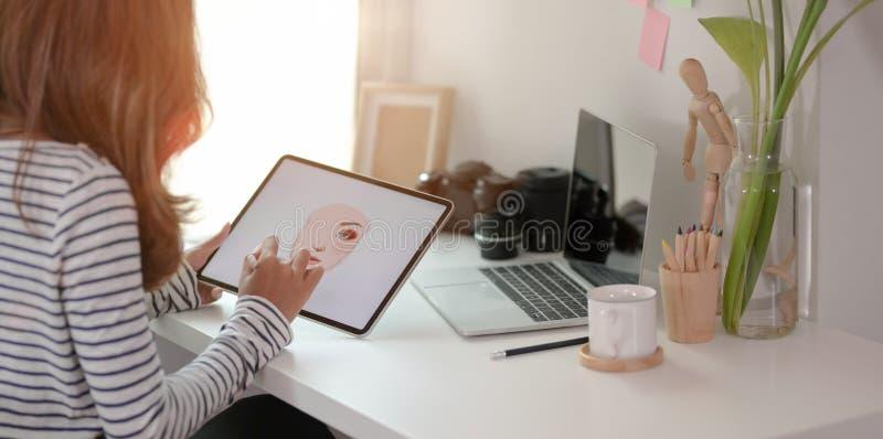专业的年轻平面设计师在现代工作场所编辑她的平板电脑项目 图库摄影