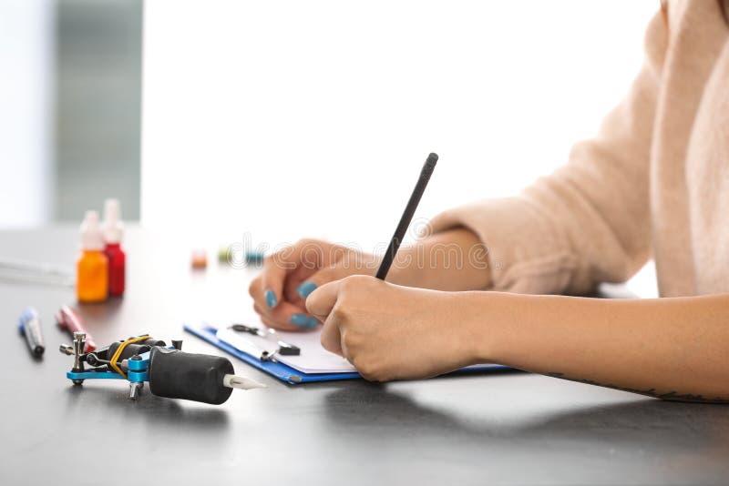 专业纹身花刺艺术家图画剪影在桌上 图库摄影