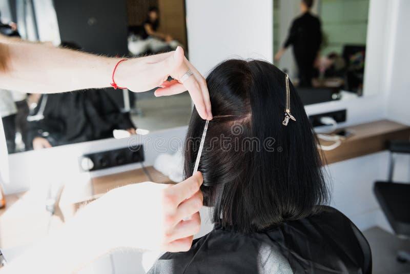 专业美发师与在沙龙的客户的头发一起使用 拉扯子线 免版税库存图片