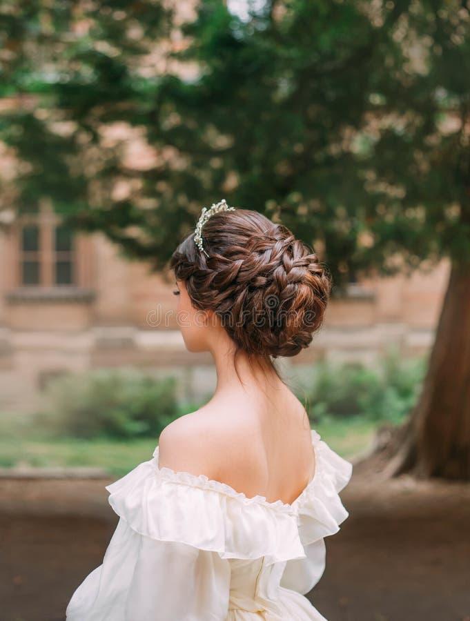 专业美发师令人惊讶的工作,长的黑褐色头发柔和的发型和冠状头饰为正式舞会或晚上 免版税库存照片