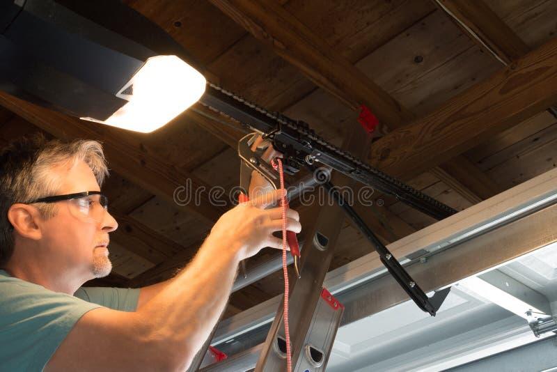 专业自动车库门开启者修理公司技术员运作的特写镜头 库存图片