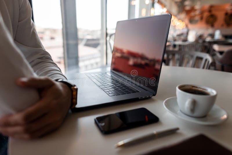 专业自由职业者人休息开会在一张桌上在有一台现代膝上型计算机的办公室有一杯咖啡的 免版税库存照片