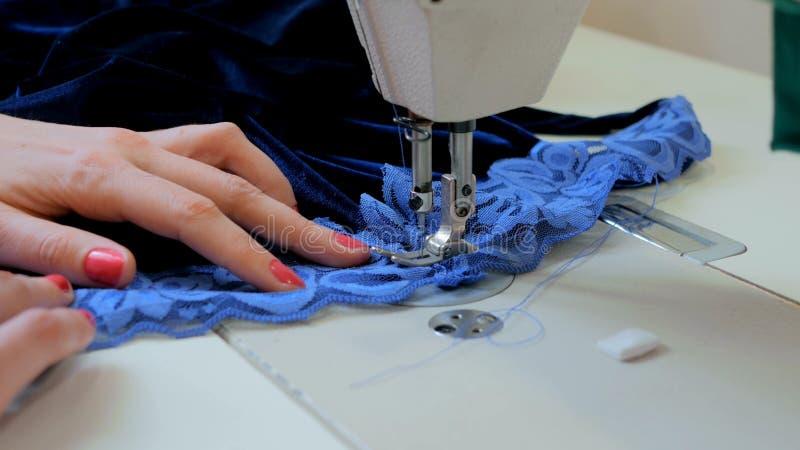 专业裁缝,有缝纫机的时装设计师缝合的衣裳 图库摄影