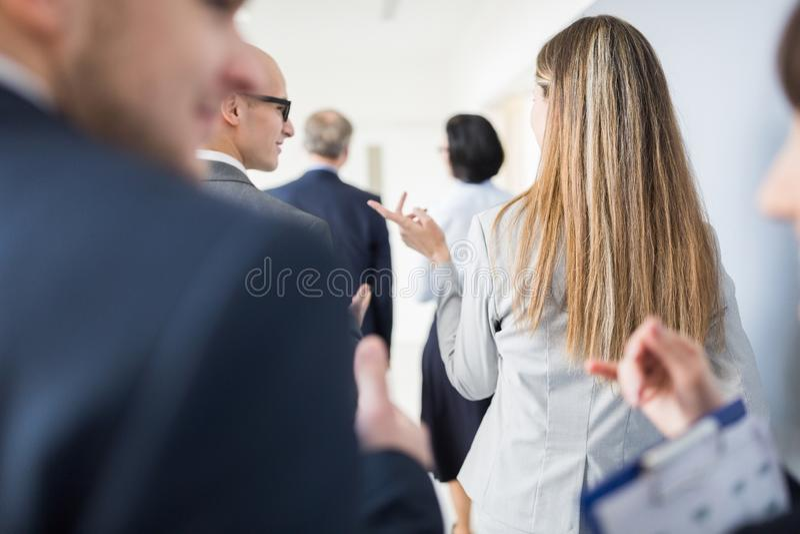 专业谈话与同事,当走与队在办公室时 免版税库存图片