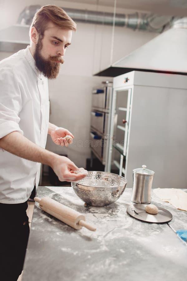 专业面包师划分面团成在桌上的片断在面包店的厨房里 免版税库存照片