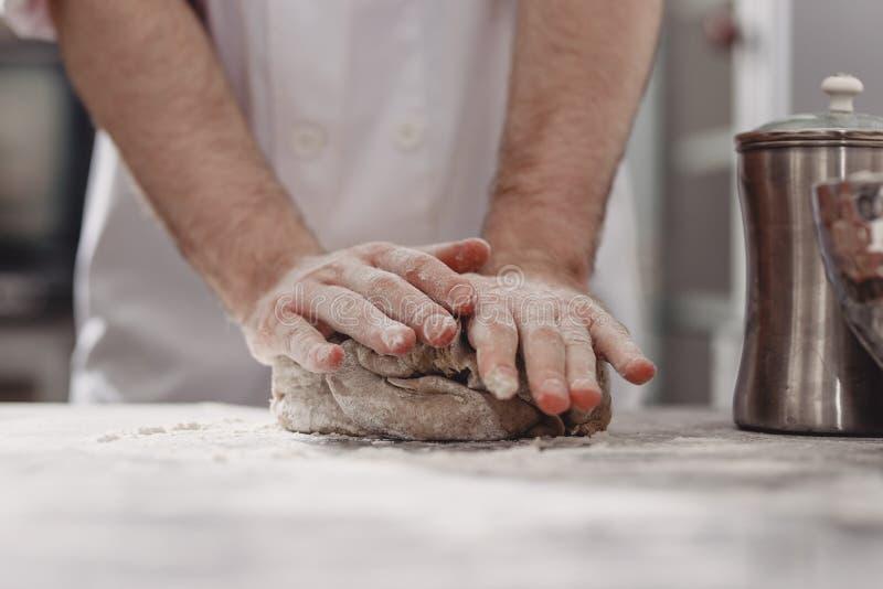 专业面包师在面包店的厨房里揉在桌上的面团 库存照片