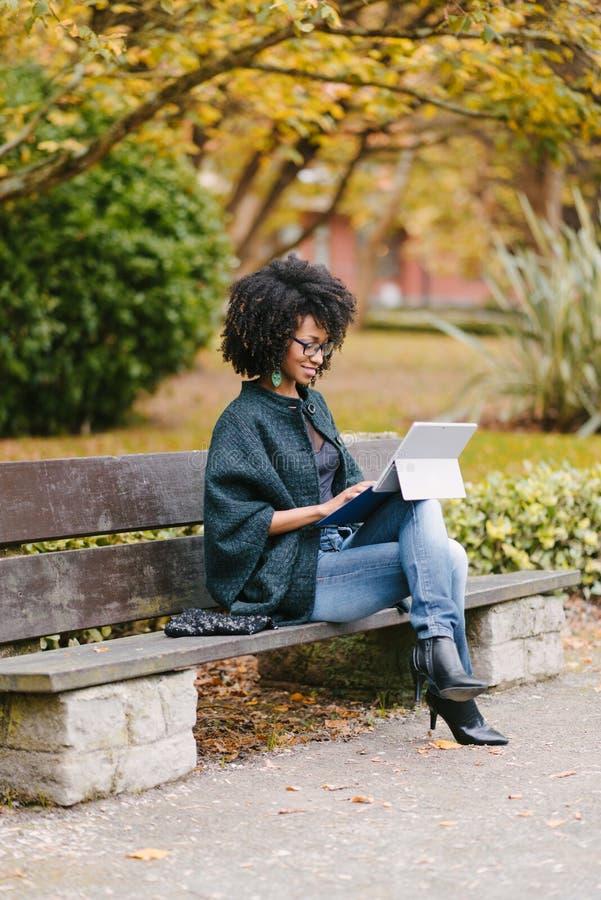 专业黑人妇女与膝上型计算机一起使用外面在秋天 免版税库存照片