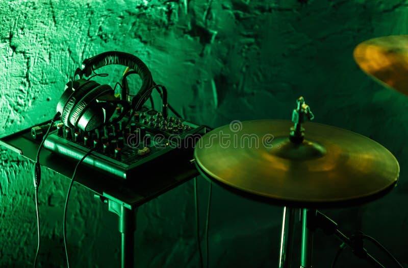 专业鼓成套工具和耳机在阶段在夜总会 图库摄影