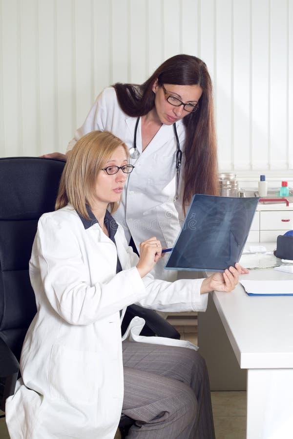 专业医疗队谈论关于肺X-射线在诊所 免版税库存照片