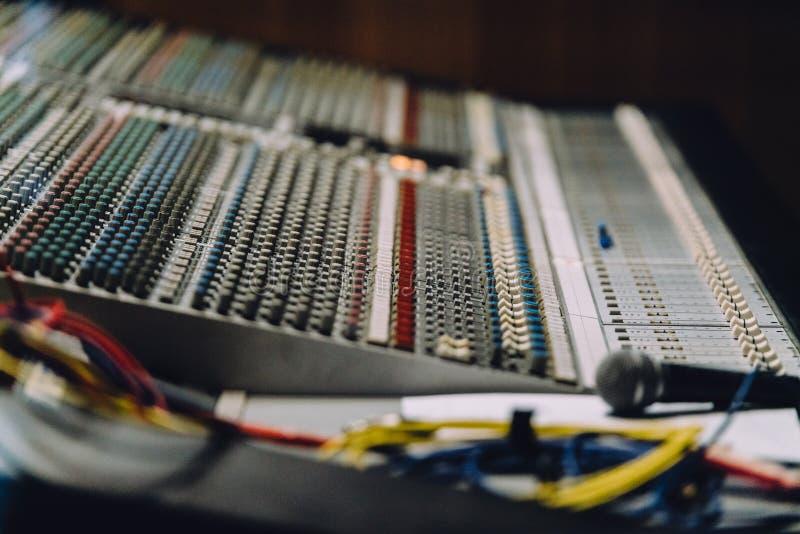 专业soundboard包括与按钮的音频搅拌器控制板和滑子、绳子和话筒在录音室 免版税库存图片