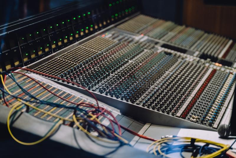 专业soundboard包括与按钮的音频搅拌器控制板和滑子、绳子和话筒在录音室 库存照片