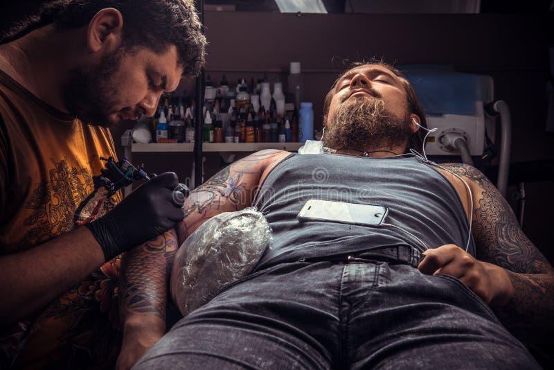 专业tattooer在纹身花刺演播室做纹身花刺 免版税库存图片