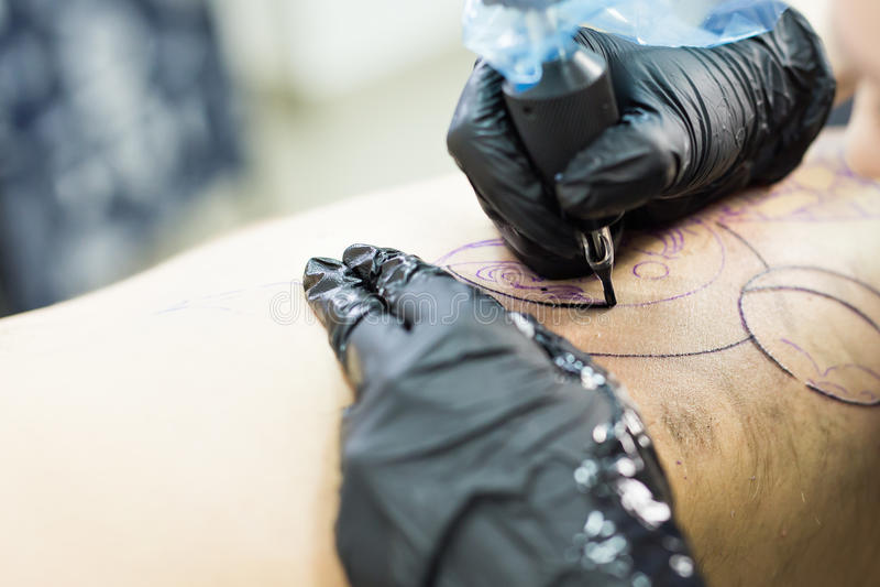 专业tattooer由特定工具关闭做与手套的纹身花刺  库存图片
