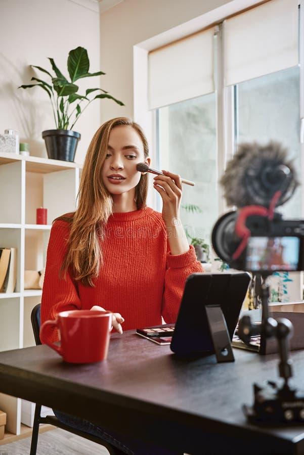 专业vlogger 使用应用的刷子的逗人喜爱和年轻女人轮廓色_,当记录组成讲解时 免版税图库摄影