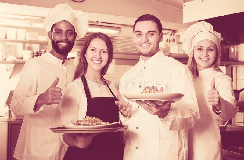 专家女服务员和乘员组在餐馆烹调摆在 库存图片