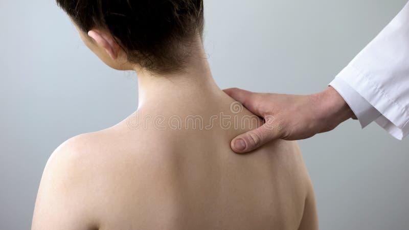 专家审查的女性后面,拿着她的肩膀,脊柱侧凸治疗 免版税图库摄影