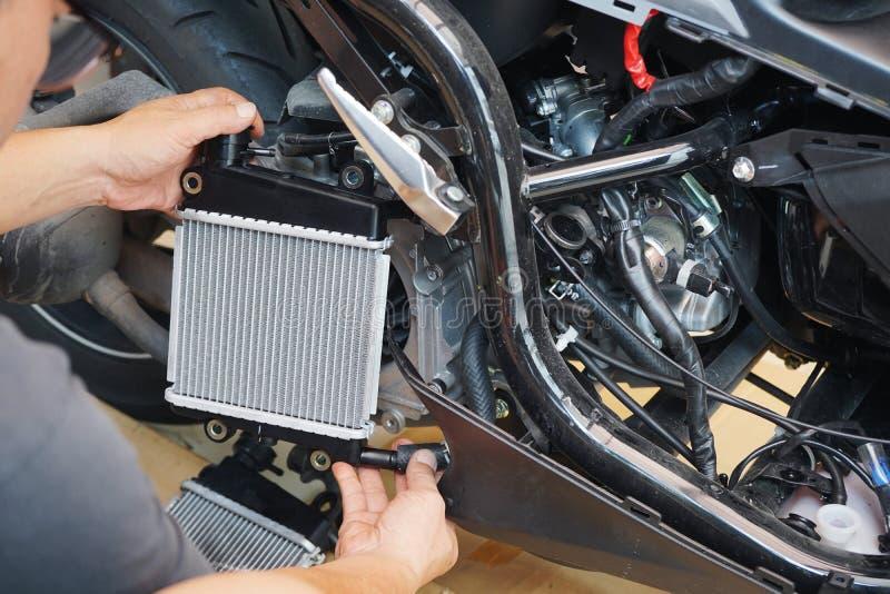 专家的技术员安装一台幅射器到摩托车或滑行车,幅射器是冷却系统的主要部分和保持 库存照片