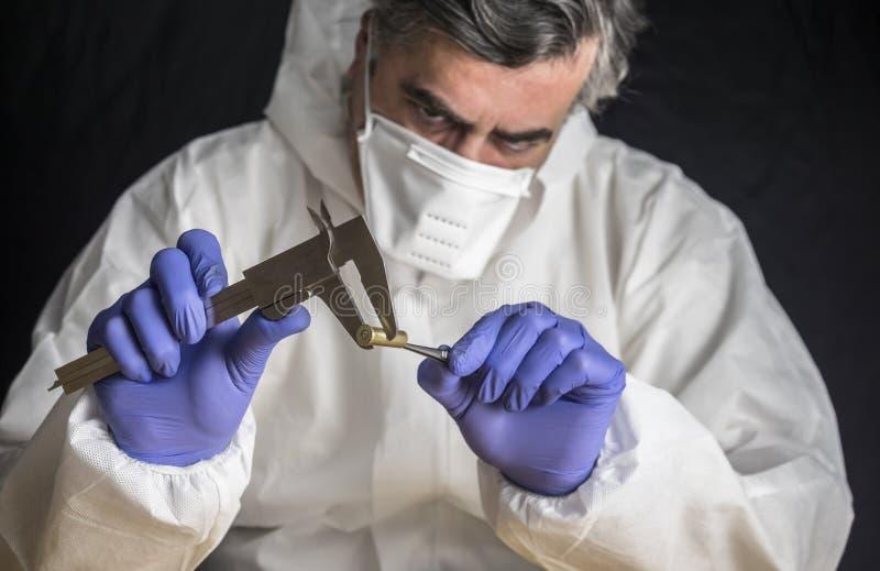 专家的警察在弹道实验室测量子弹口径 免版税库存图片