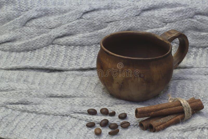 专属古色古香的黏土茶杯、芬芳桂香和烤咖啡豆在轻的被编织的背景 图库摄影