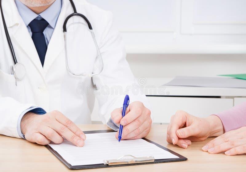专心地听一位男性医生的患者解释耐心症状或问问题,他们一起谈论文书工作  免版税库存照片