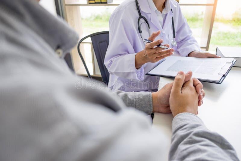 专心地听一位男性医生的患者解释耐心症状或问问题,他们一起谈论文书工作  库存照片