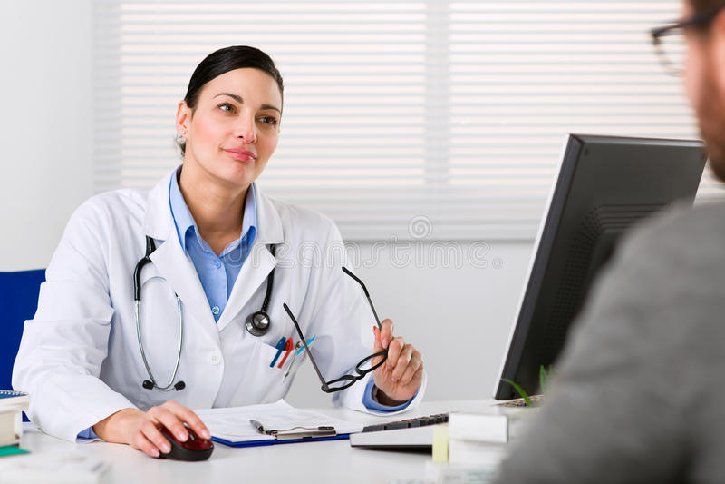 专心地听年轻女性的医生 图库摄影