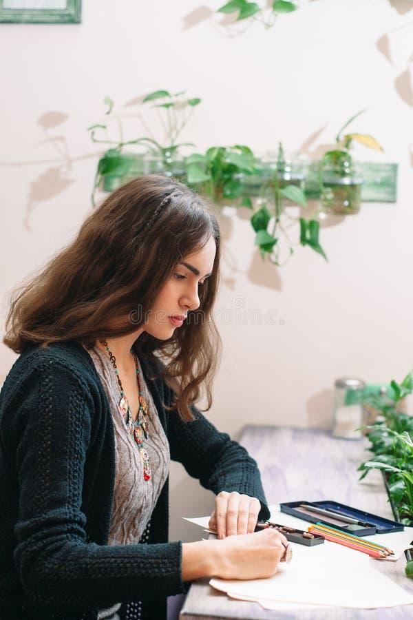 专心地画侧视图的年轻女性画家 免版税图库摄影