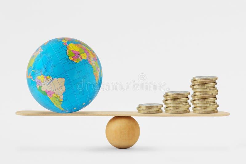 世界地球和硬币堆在平衡等级-平衡的概念在星球健康和经济增长之间 库存图片