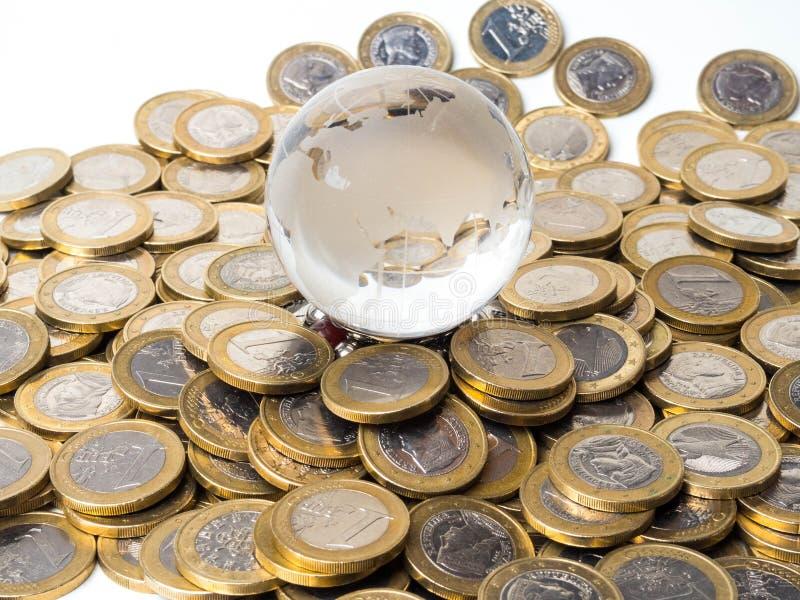 世界地球和硬币堆-平衡的概念 库存图片