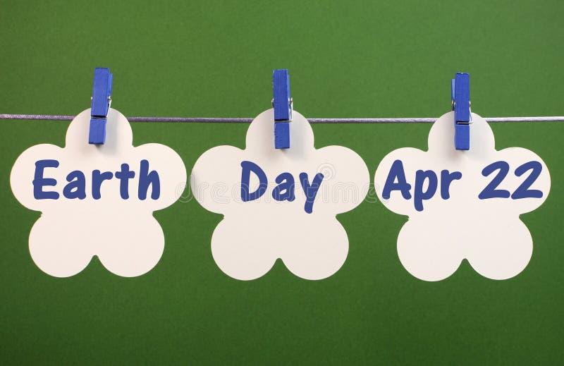 世界地球日,问候4月22日,横跨白花被写的消息拟订垂悬从在线的钉 免版税库存图片
