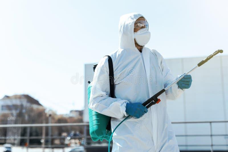 世界大流行病 防护服和口罩中的消毒剂,将消毒化学品存放在室外 库存图片