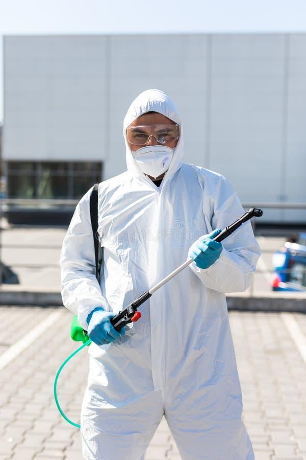 世界大流行病 防护服和口罩中的消毒剂,将消毒化学品存放在室外 库存照片