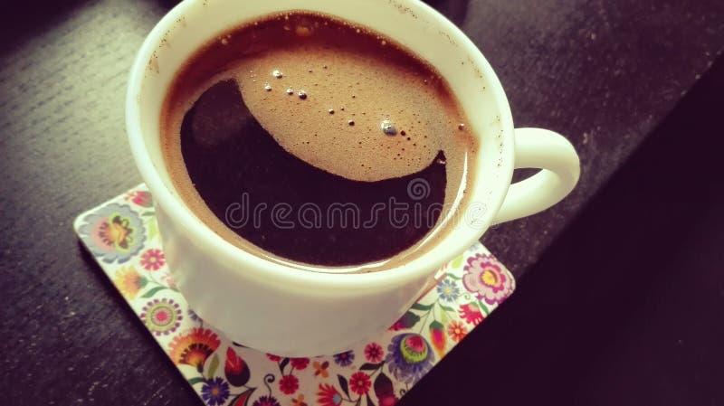 世界微笑-微笑在一个白色杯子的咖啡在黑书桌上的颜色垫 免版税库存图片