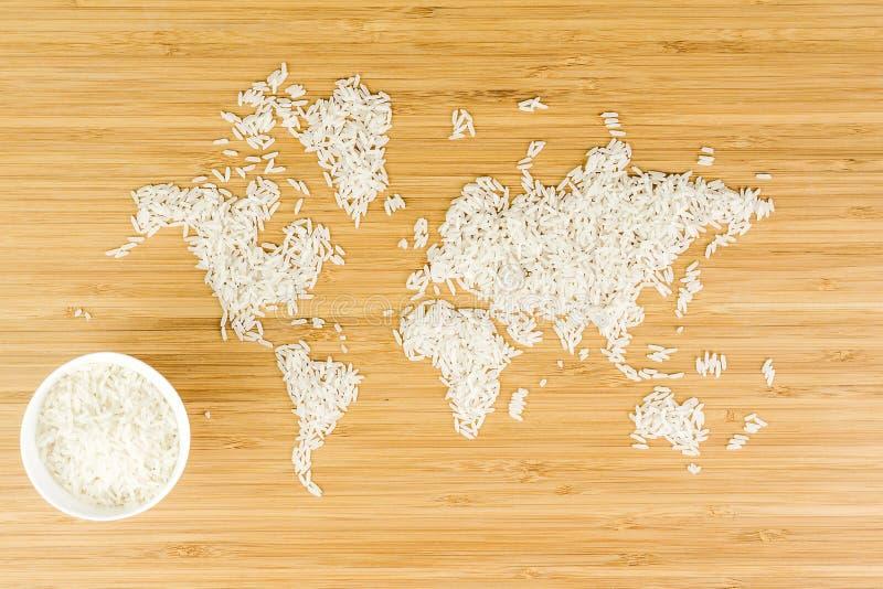 世界的地图由与白色陶瓷碗的白米制成 图库摄影
