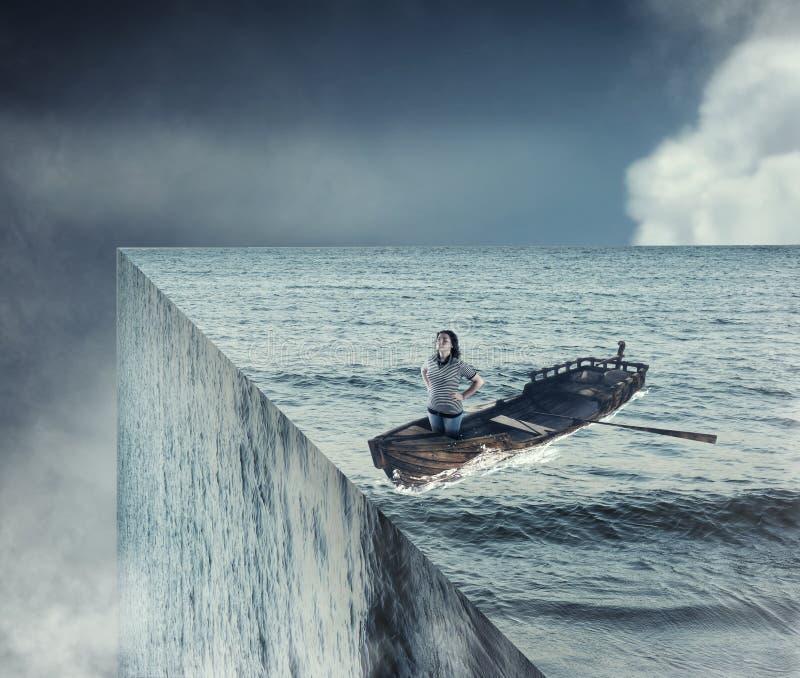 世界的末端 在一条小船的女孩风帆在海洋 免版税库存照片