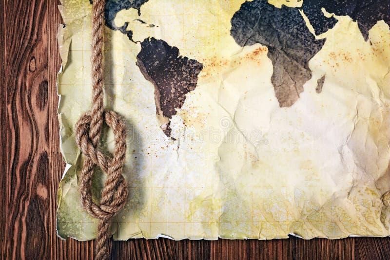 世界的老葡萄酒地图在黄色减速火箭的被弄脏的纸的与结绳索 库存图片