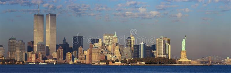 世界贸易全景日落视图耸立,自由女神像、布鲁克林大桥和曼哈顿, NY地平线 库存照片