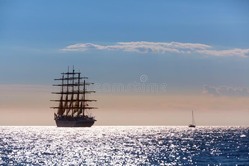 世界` s最大的帆船离开在日落在公海 库存照片