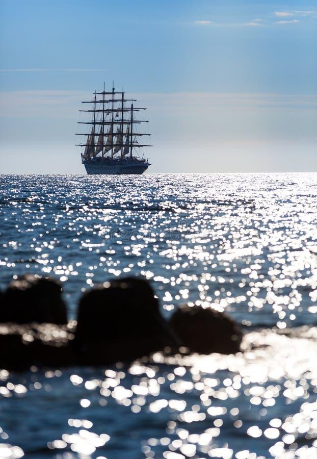 世界` s最大的帆船离开在日落在公海 免版税库存图片