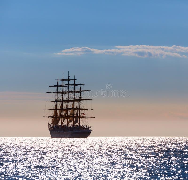 世界` s最大的帆船离开在日落在公海 图库摄影