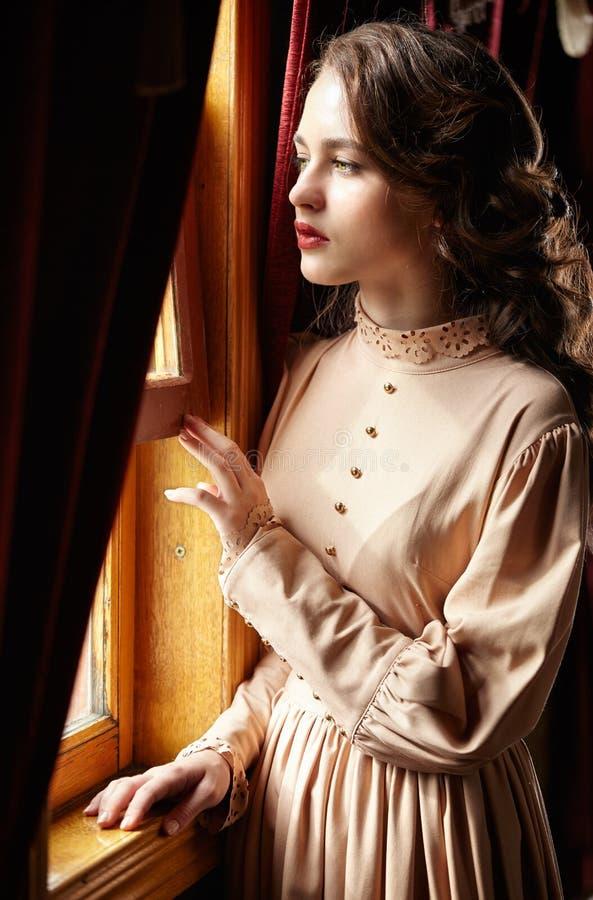 20世纪初替换者米黄葡萄酒礼服的少妇  免版税图库摄影