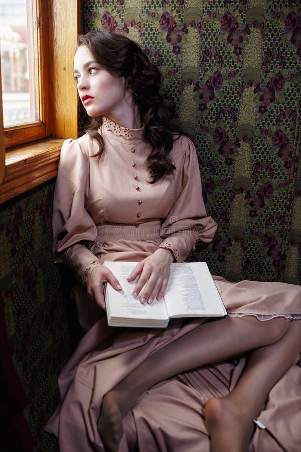 20世纪初读书米黄葡萄酒礼服的少妇  免版税库存照片