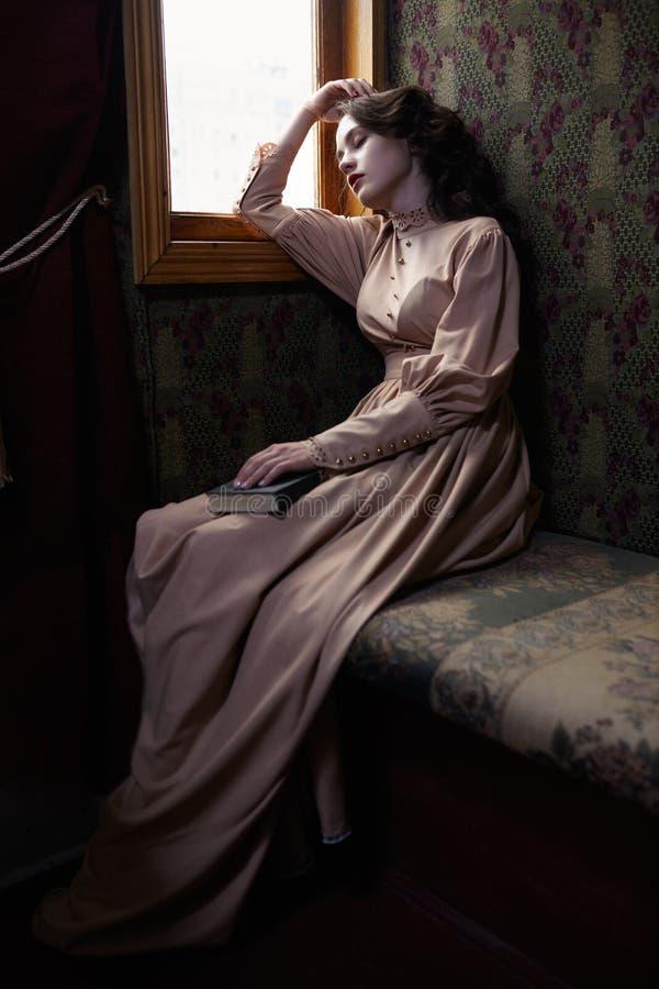 20世纪初sleapin米黄葡萄酒礼服的少妇  免版税图库摄影