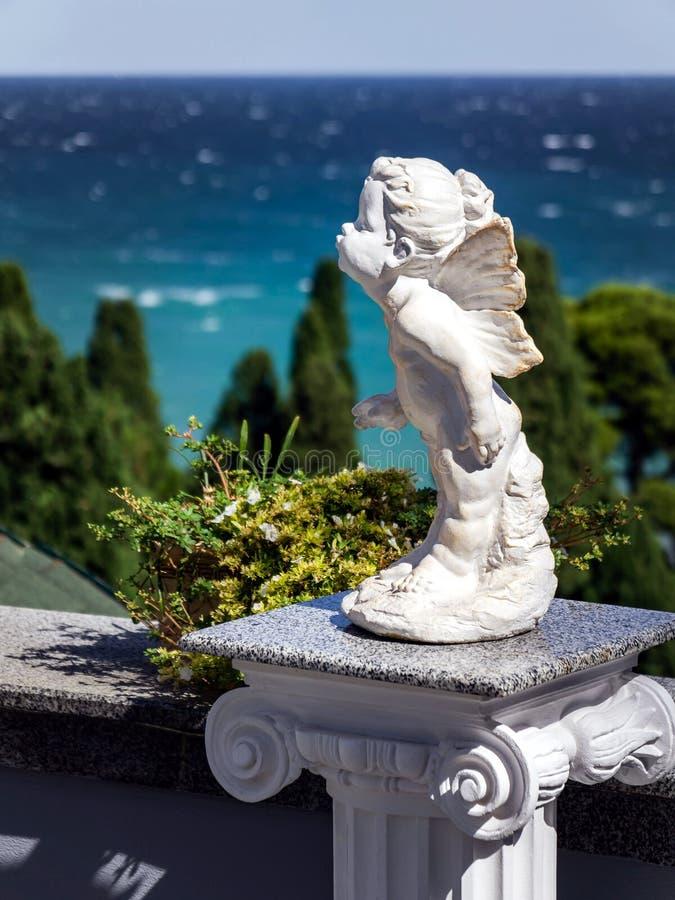丘比特一个小雕象在绿色树和蓝色海背景的  免版税库存照片