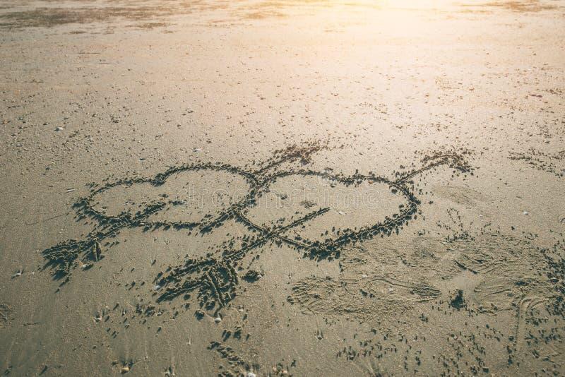丘比特在海海滩的标志凹道双爱心脏箭头  免版税库存图片