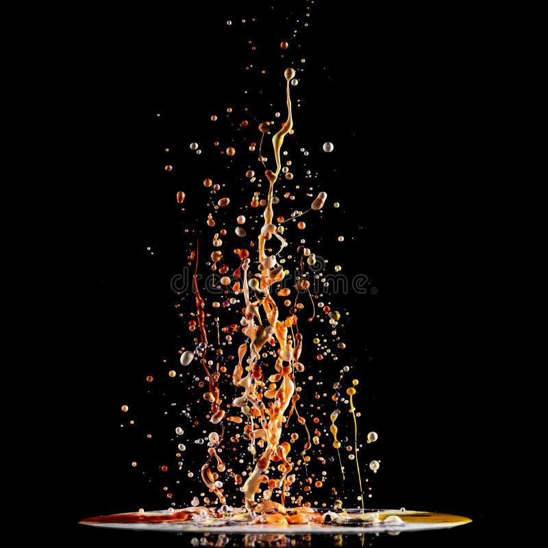 丙烯酸漆,多彩多姿的油漆爆炸,在黑色的抽象背景飞溅  库存图片