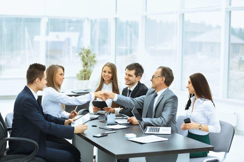 业务会议在商务伙伴桌和握手上  免版税图库摄影