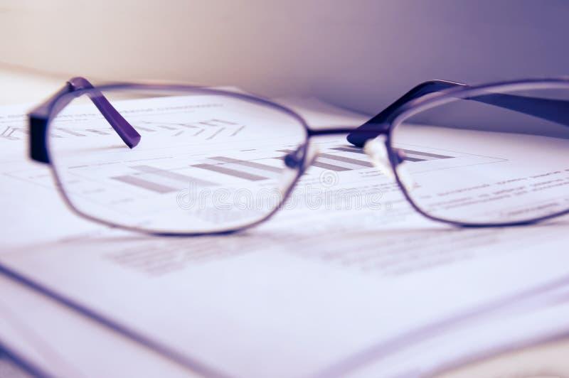 业务报告的准备 堆文件、一个笔记本和玻璃在桌上 免版税库存图片