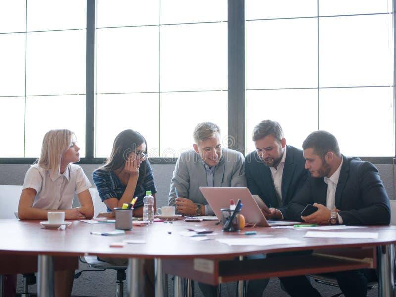 业务顾问,当工作在队时 一个小组年轻工人在一次会议上在公司会议室 图库摄影