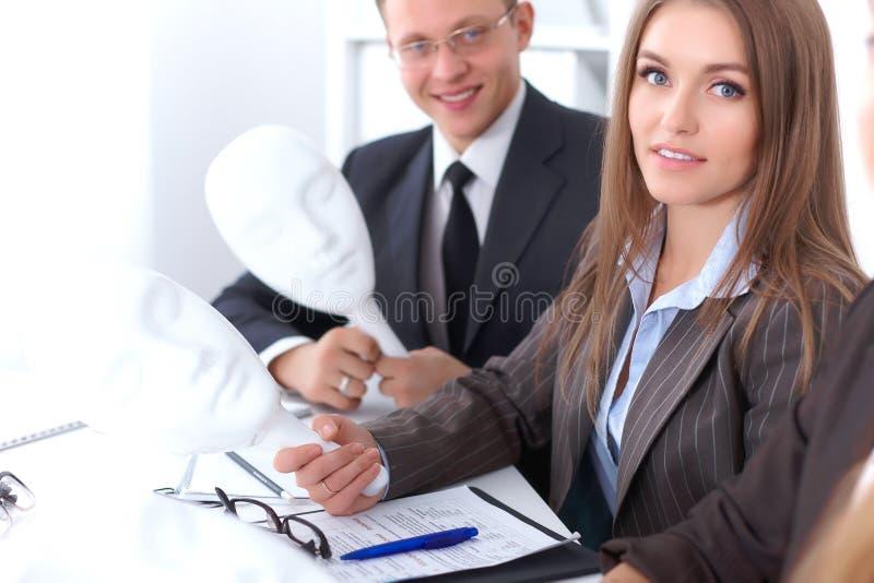 业务组会议人 在Th期间,商人掩藏他们的情感在信心下面具  免版税库存图片